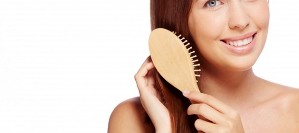 smiling-woman-brushing-her-healthy-hair_1098-4047